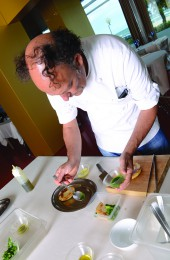 Moreno Cedroni guarnishing the celerianc and lime puree with arugula sauce