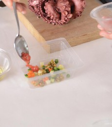 Plating the base of the octopus in green salsa